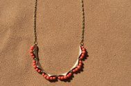 Vintage gold chain with a vintage gold and coral colored bead bracelet as the centerpiece of the bracelet.